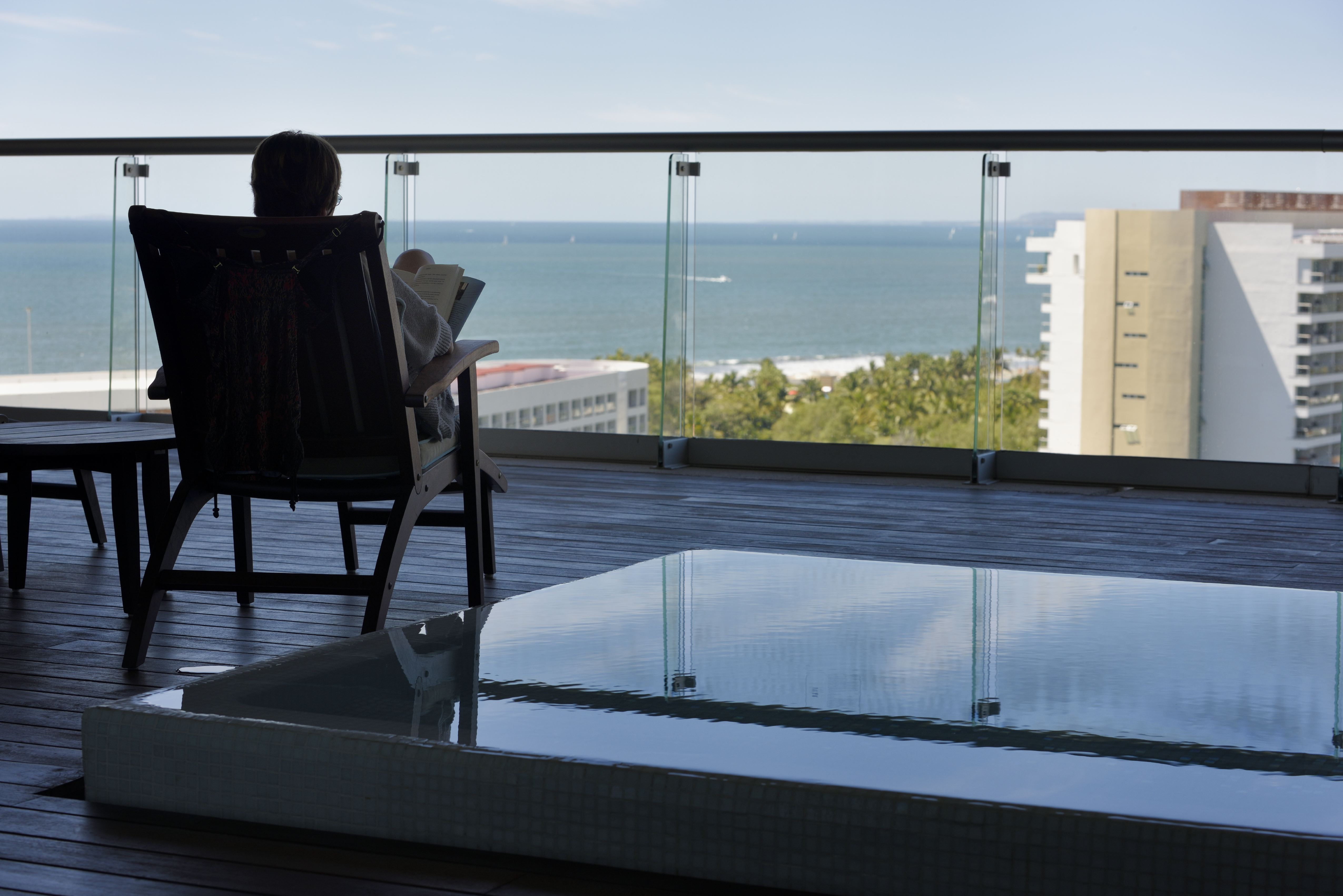 Tourist reading a book on the balcony of the penthouse suite Vidanta Nuevo Vallarta Mexico
