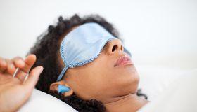 Woman sleeping in eye mask and ear plugs