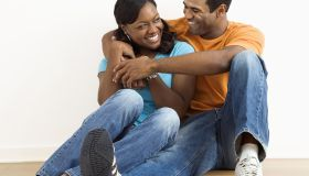 Happy, smiling African American couple sitting on floor snuggling.