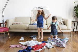 Young boy and girl with laundry basket over her head standing in front of sofa, laundry scattered on hardwood floor.