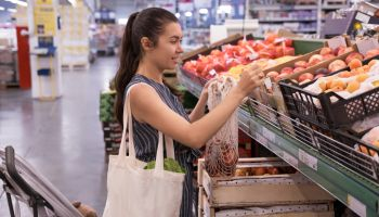 Woman with grocery eco bag of vegetables in a supermarket background.