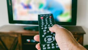 Close-Up of Woman's Hand Pointing Remote Control at TV