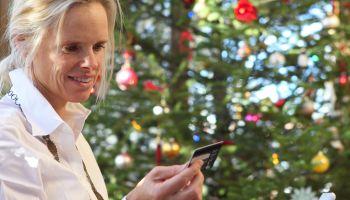 Online Christmas shopping: woman besides xmas tree